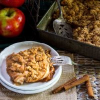 Top angled view of a slice of apple crisp sitting on a stack of two white plates over a piece of burlap. The pan of crisp sits in the background next to fresh apples and cinnamon sticks.