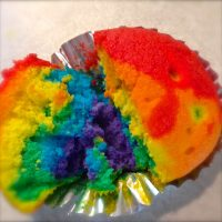 A close up of a rainbow cupcake.