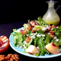 A light blue plate holding a green lettuce salad tossed with grilled peaches. A carafe of Honey Jalapeno dressing, a grilled peach half,  and toasted walnuts sit next to the plate.
