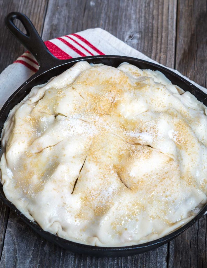 Pie crust dusted with sugar and sliced to vent the apple pie it covers in a cast iron skillet