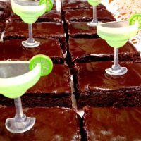 Sliced chocolate brownies frosted in chocolate frosting. Plastic margarita glasses decorate the brownies.