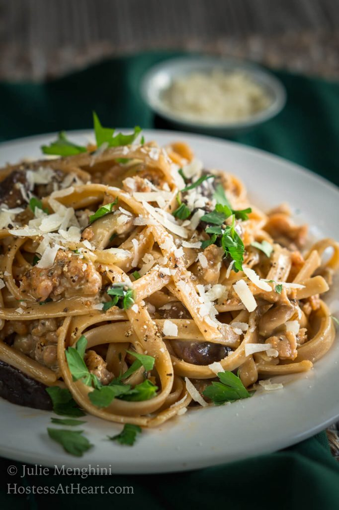 Close up side view of a white plate filled with Fettuccine pasta combined with sausage, mushrooms, and cheese and garnished with fresh parsley. A block of parmesan sits over a grater next to a wire dish of grated cheese over a green napkin.
