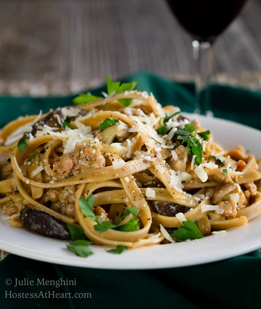 Side view of a white plate filled with Fettuccine pasta combined with sausage, mushrooms, and cheese and garnished with fresh parsley. A block of parmesan sits over a grater next to a wire dish of grated cheese over a green napkin. A glass of wine sits in the background.
