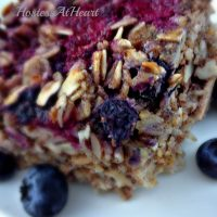 A slice of Berry Nut Baked oatmeal with fresh blueberries scattered around it.