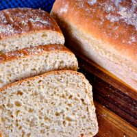 A loaf of English Muffin Bread that has slices cut from the front next to a whole loaf of bread.