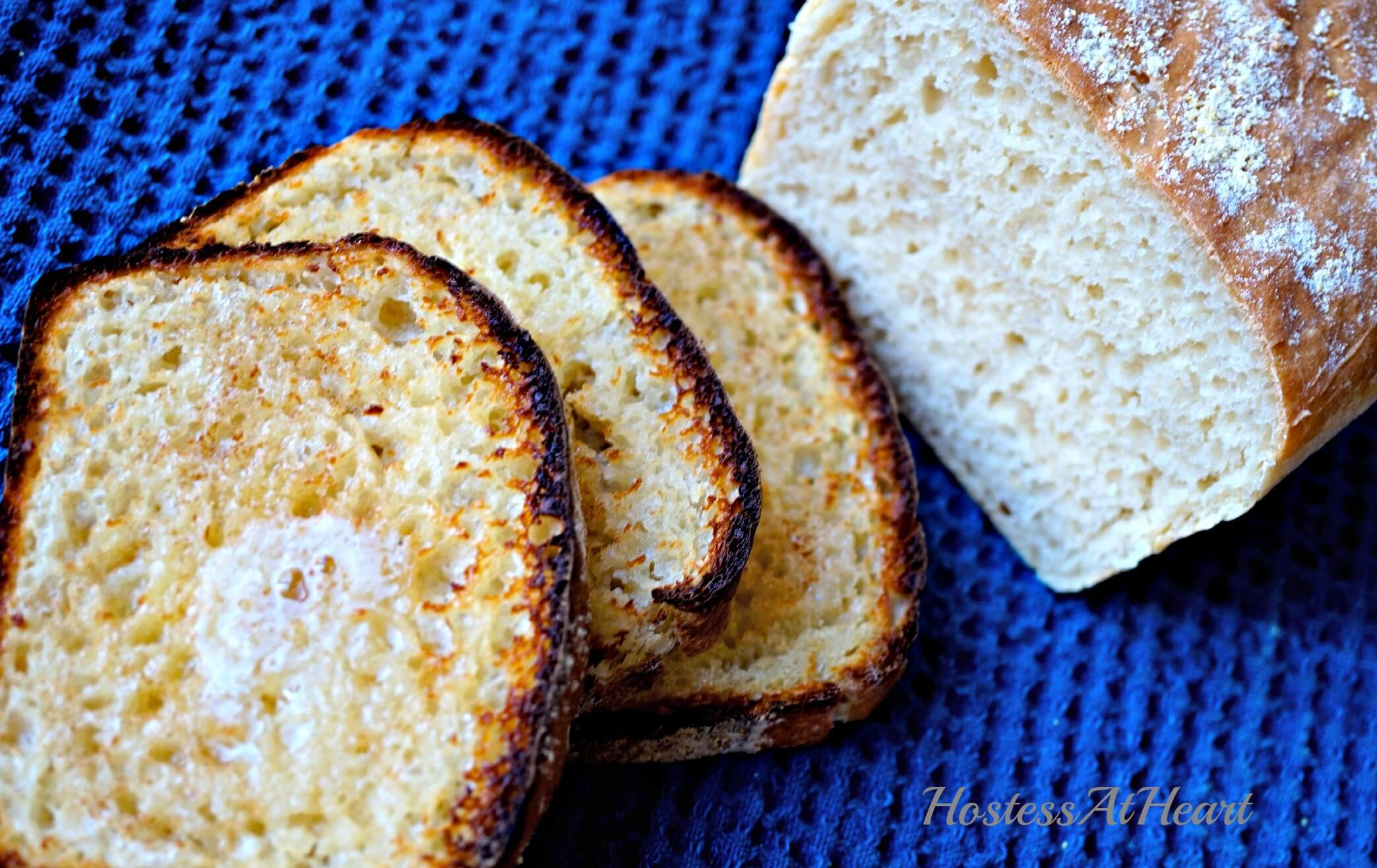 Slices of toasted English Muffin Bread sitting next to the cut loaf.