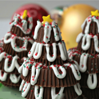Three Christmas trees made from Reeses Peanut Butter cups with Ornaments in the background.
