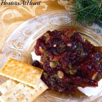 A glass plate topped with a brick of cream cheese that's topped with a Cranberry Pistachio sauce. Crackers sit off to the side.