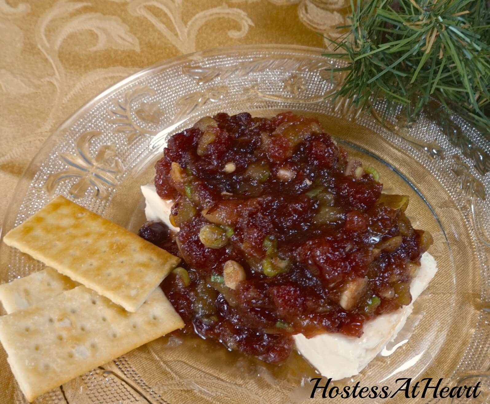 A glass plate topped with a brick of cream cheese that\'s topped with a Cranberry Pistachio sauce. Crackers sit off to the side.