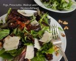 close up of a salad with shaved parmesan, figs, walnuts on a plate