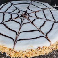 An Esterhazy torte with a spiderweb design over the top and the sides pressed with crushed nuts.