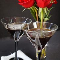 Two cocktail glasses filled with Espresso Chocolate Martinis. Red roses sit in the background.A glass of wine on a table, with Manhattan and Chocolate