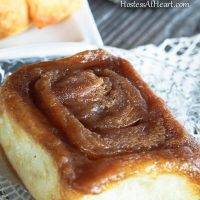 A caramel roll sitting on a glass plate.