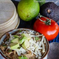 A bowl Pulled Pork Green Chile Verde surrounded by fresh lime, tomato, avocado, and tortillas.