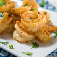 A close up of a white plate of shrimp garnished with cilantro.
