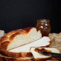A loaf of Hungarian Egg Twist Bread with the front slices cut from the front. A jar of jam sits in the background and a knife with jam sits on the front slice of bread.