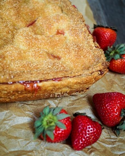 Square slab Strawberry pie sitting on a piece of parchment surrounded by fresh strawberries.