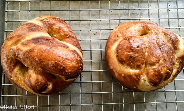 Pretzel buns sitting on a cooling rack.
