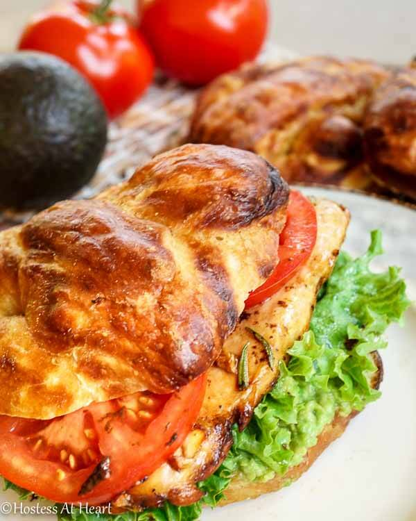 A grilled chicken sandwich on a pretzel bun layered with lettuce and tomato. Fresh avocado and tomatoes sit in the background.
