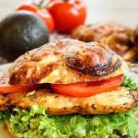 A grilled chicken sandwich on a pretzel bun layered with lettuce and tomato. Fresh tomatoes and an avocado sits in the background.