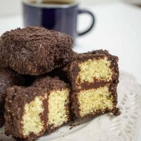 A plate of chocolate lamingtons in front of a cup of coffee. Two of the lamingtons are cut in half showing yellow cake layered with chocolate frosting.