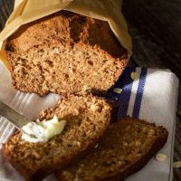 A loaf of Applesauce Oatmeal bread wrapped in parchment paper. The front two slices it in front of the loaf.