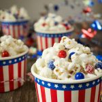 Side view of candied popcorn with pieces of red and blue chocolate candies in a 4 patriotic bowls.