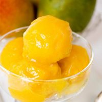 Scoops of mango sorbet in a glass bowl sitting in front of fresh mangos.