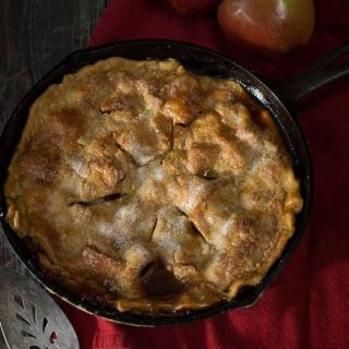 top view of whole apple rhubarb pie with two raw apples