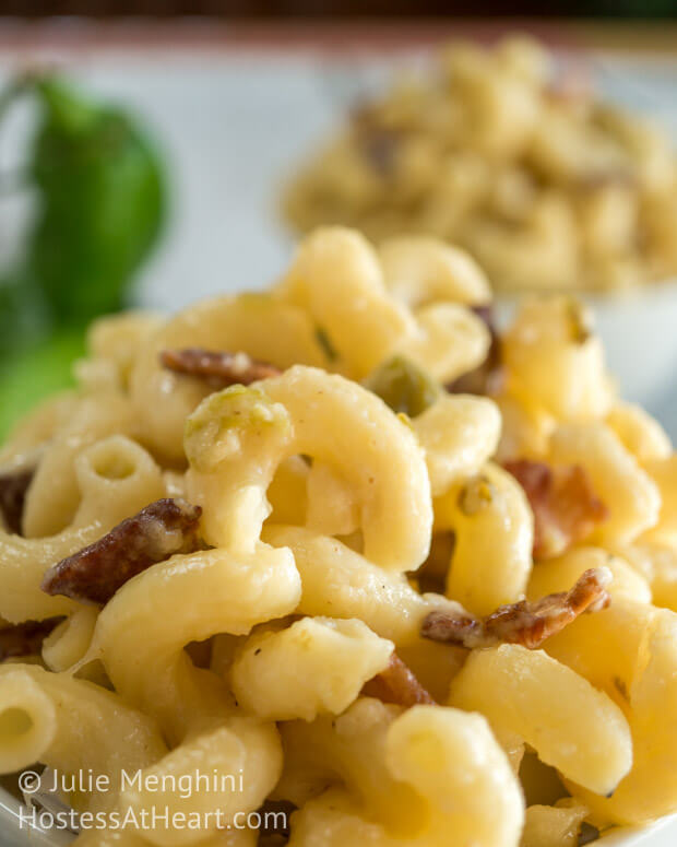 A close-up side view of macaroni and cheese with hatch chilies and bacon. A second bowl sits in the background.
