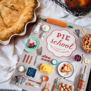 A book on pie sits next to a baked pie.