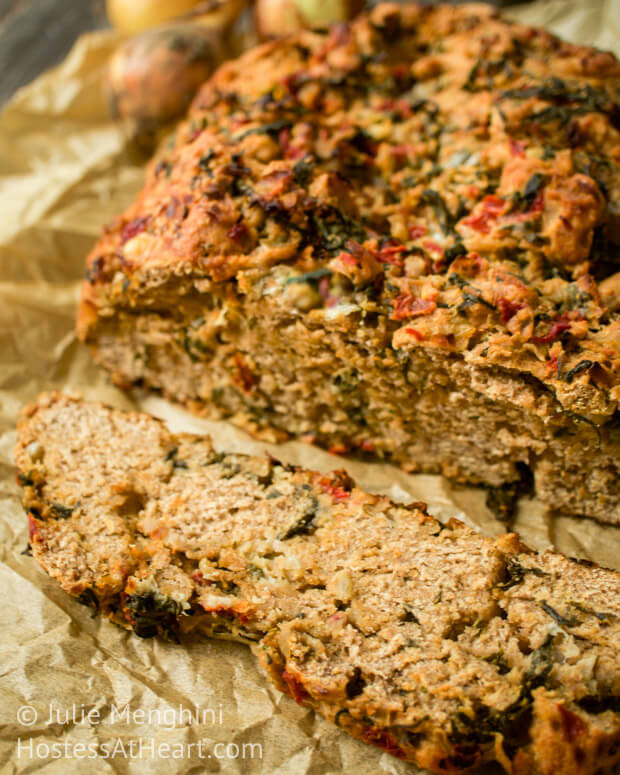 A close up of a loaf of Whole wheat bread stuffed with spinach, onion, and red pepper.