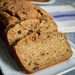 A loaf of apple banana bread on a white platter. A blue striped napkin sits in the background.