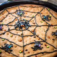 Chocolate chip baked in a cast-iron skillet and topped with decorated with a piped black spider web with piped spiders and sprinkles.