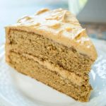A piece of layered Spice Cake with Peanut Butter frosting between the layers and over the top on a white plate.