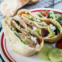 Two open pita halves filled with sliced chicken, onion kalamata olives, cucumbers, and Feta cheese sits on a white plate. Cooked pitas sit on a cooling rack in the back.