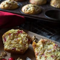 A cranberry-Orange muffin that's been cut in half showing it's the soft center. A muffin tin sits in the back filled with more muffins.