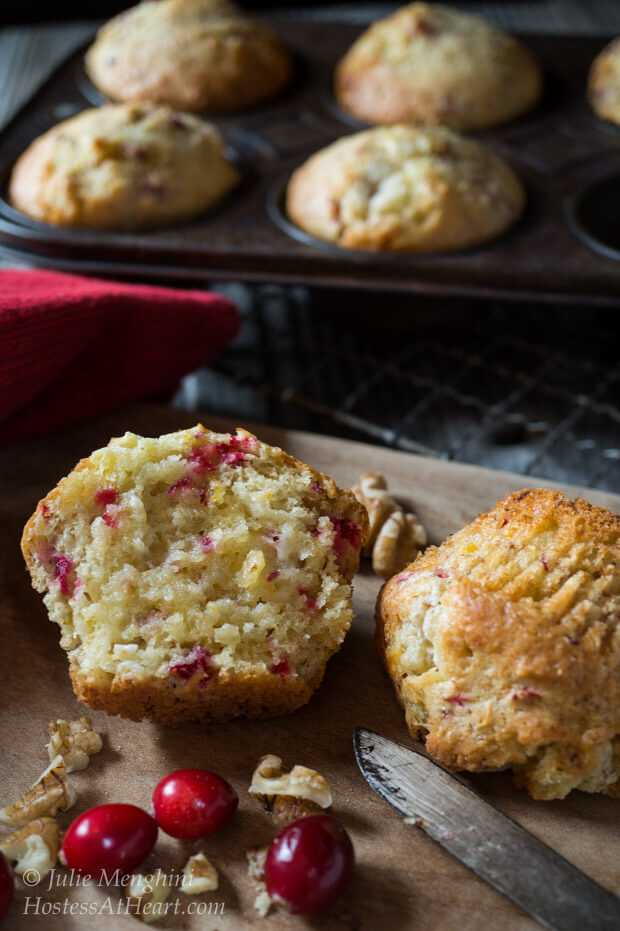 A cranberry-Orange muffin that\'s been cut in half showing it\'s the soft center. A muffin tin sits in the back filled with more muffins.