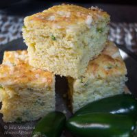 Three slices of Jalapeno Cheddar Cornbread surrounded by fresh jalapenos.