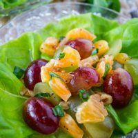 Butter lettuce leaf filled with a fruit salad made of grapes and clementines sitting on a glass plate.