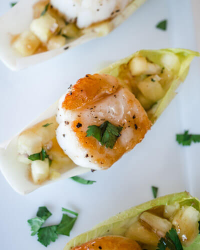 Scallops with Pineapple Salsa and Plum Wasabi Drizzle sitting in an endrive leaf