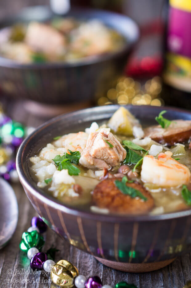 Large pieces of duck, sausage and shrimp  sit in a spicy broth with colorful Mardi Gras beads surrounding the bowl.