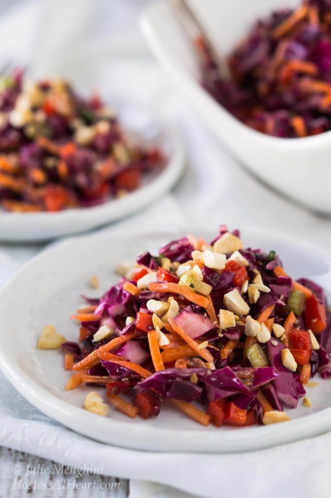 The beautiful colors in this Asian Cabbage Salad make for a show stopper dish. The crunchy veggies and cashew nuts are tossed in a ginger sesame vinaigrette for one delicious salad | HostessAtHeart.com