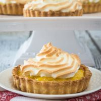 A Pineapple Cream Meringue Tart sitting on a white plate in front of a cake plate filled with three more tarts.