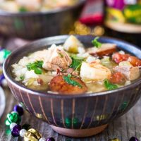 A bowl of Shrimp, Duck and Andouille Gumbo garnished with fresh parsley in a stiped bowl with New Orleans beads spread around it.