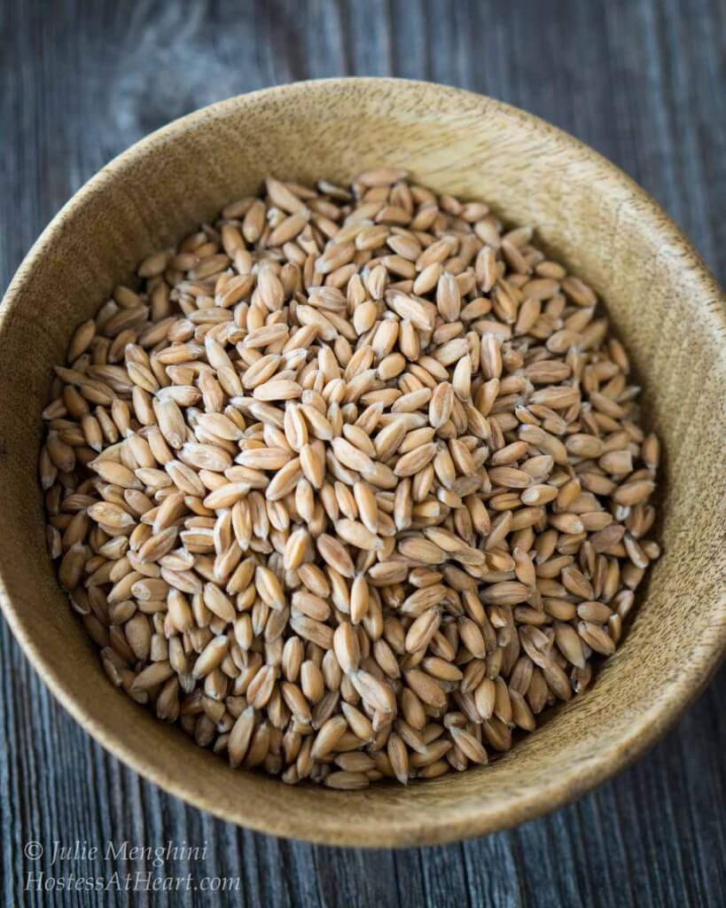 Wooden bowl filled with spelt grain.