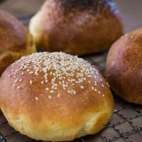 Angled view of brioche buns over a cooling rack and topped with sesame seeds or poppy seeds. Some are left plain.