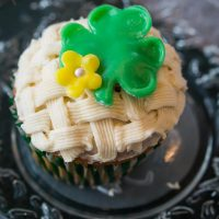 Cupcake decorated with a basketweave pattern. A green Shamrock and flower sit on the top. The cupcake sits on a metal plate.
