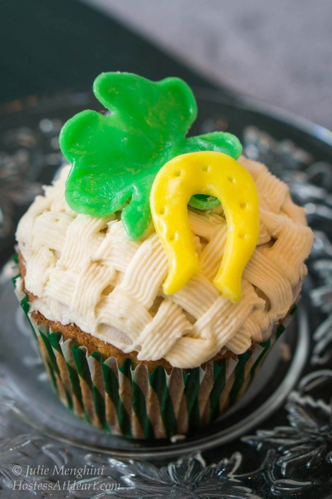 Cupcake decorated with a basketweave pattern. A green Shamrock, horseshoe, and flower sit on the top. The cupcake sits on a metal plate.