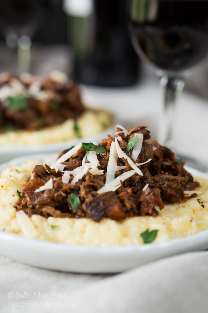 Side view of a lamb Ragu on a pile of cheesy polenta and garnished with shredded cheese and chopped parsley sitting on a white plate. A second plate and a wine glass sit in the background.